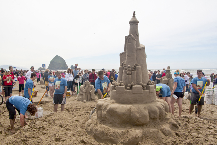 Participants apply the finishing touches to a large sculpture at the 2013 Sandcastle Contest in Cannon Beach, Oregon.