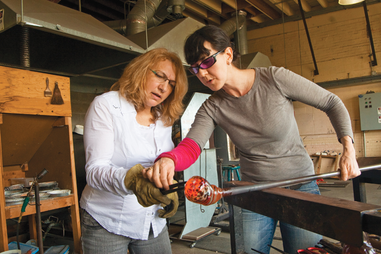 Kelly Howard works on a small vessel at the Jennifer Sears Glass Art Studio in Lincoln city where visitors can blow their own piece of glass art. Howard