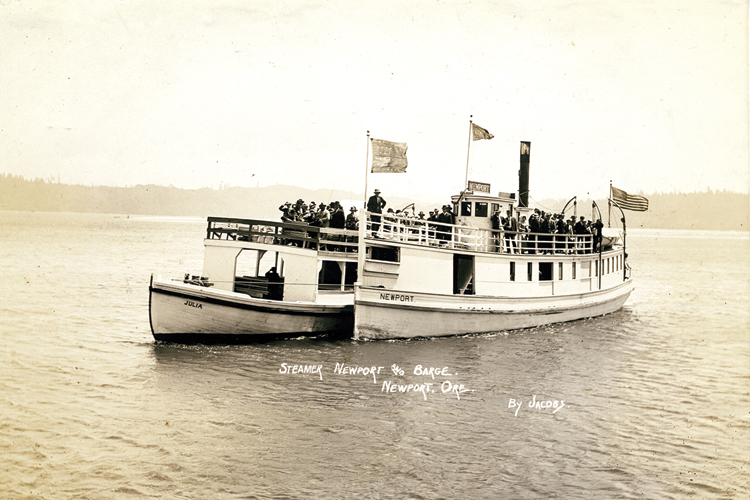 The steamer ferry Newport towing the passenger barge Julia, likely traversing Yaquina Bay near Newport, Oregon. Circa 1920, photo courtesy of Oregon State Library.