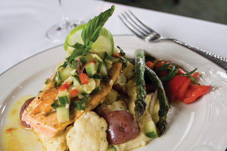 The summer menu at Bridgewater Bistro in Astoria features a seared filet of salmon dusted with Indian spices, topped with a fresh cucumber relish featuring red pepper, Thai basil and onion, all on a bed of roasted potatoes and cauliflower.