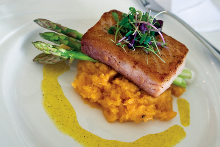 A colorful dish from The Bay House in Lincoln City: pan-seared Opah with vanilla-toasted tangerine sauce on a bed of mashed rutabaga.