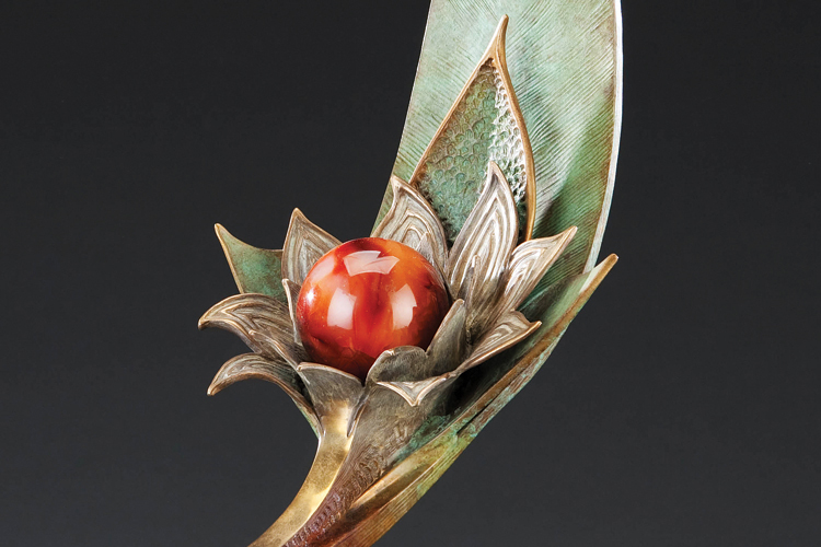 """Flow of Life,"" a bronze sculpture by Carolyn Sato incorporates a variety of patinas and a polished orb of carnelian."