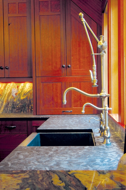 Textured stone countertops contrast with the high shine of the kitchen fixtures in this Astoria home.