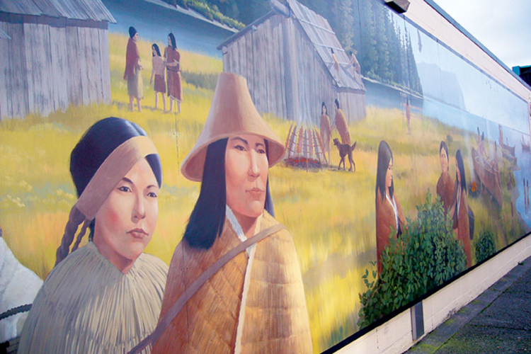 A mural on the north side of the commercial building at Broadway and Holladay Drive in Seaside depicts the daily life of Clatsop and Nehalem tribes.